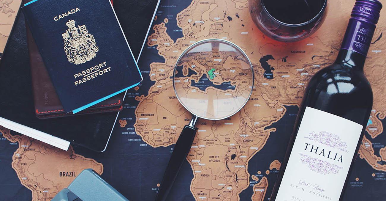 Bild zeigt einen Reisepass, eine Flasche Wein, EIne Lupe und eine Weltkarte