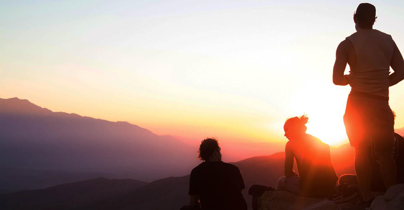 Drei Menschen auf einem Berg bei Sonnenuntergang