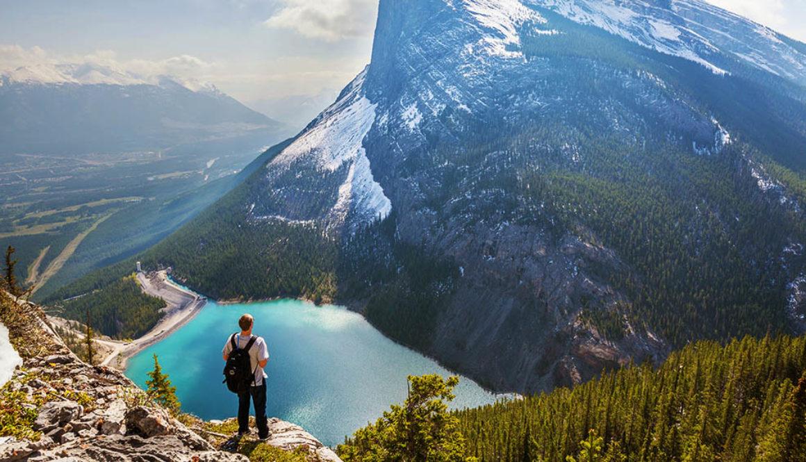 Bild zeigt einen Wanderer vor einem See und Bergen