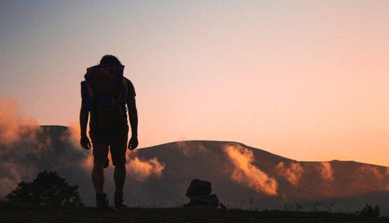 Bild zeigt einen Mensch mit seinem Rucksack beim Wandern