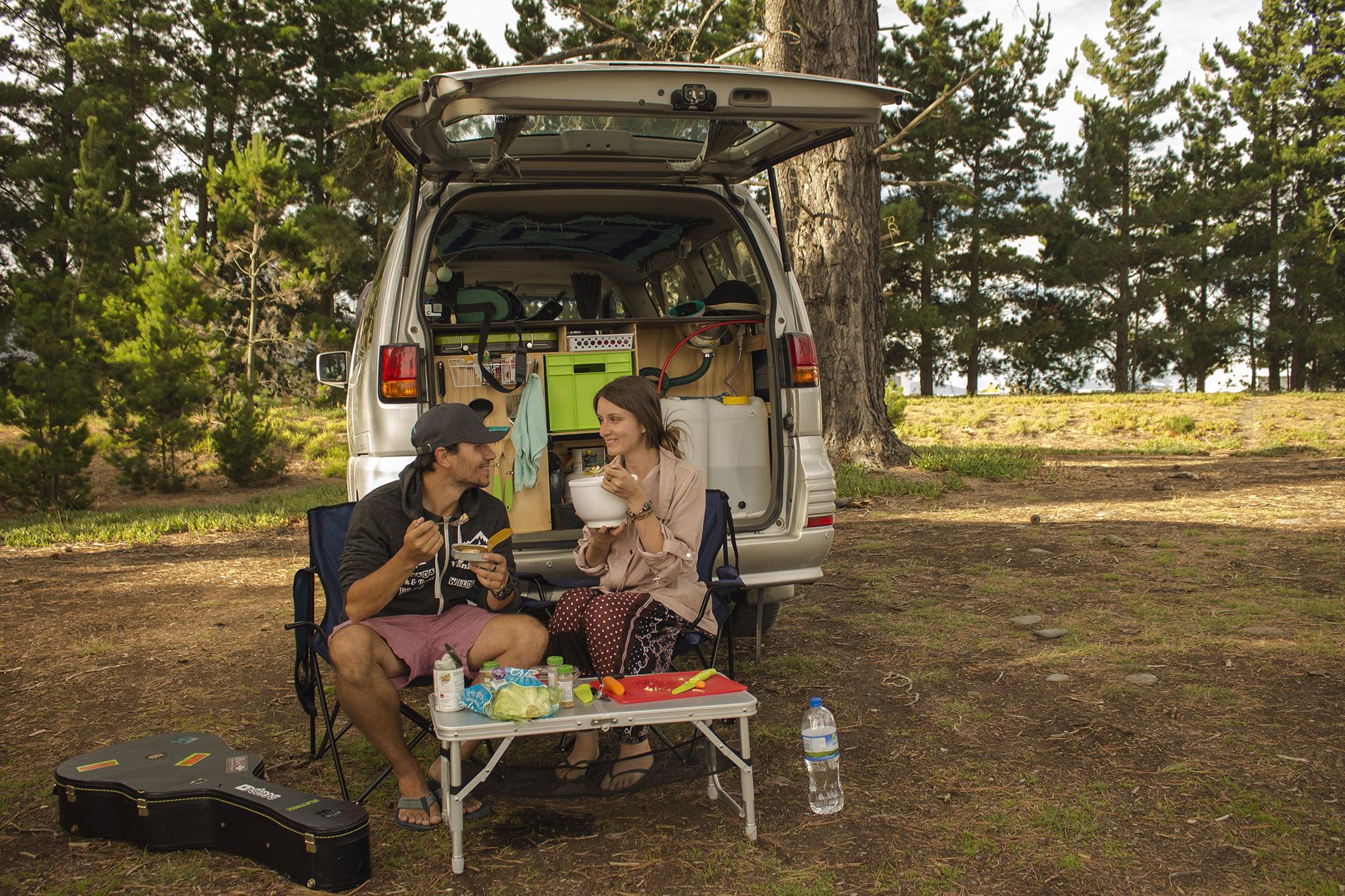 Bild zeigt Daniel und Christina vor ihrem Campervan beim Kochen
